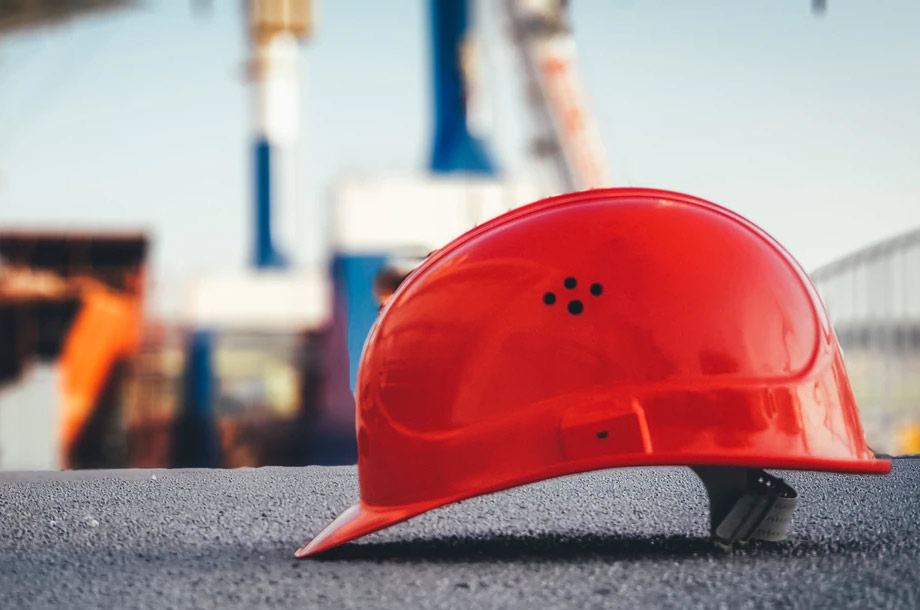Red hard hat sitting on ground | Workers' Compensation